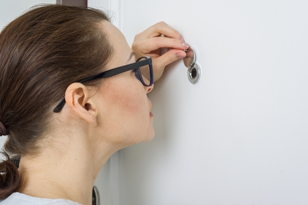 Woman looks through the peephole of the front door in the apartment. Stockfoto