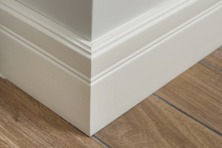 Molding in the interior, baseboard corner. Light matte wall with tiles immitating hardwood flooring. Banque d'images