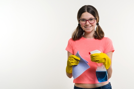 Cleaning day, spring cleanup, housework concept. Girl teenager in yellow gloves with rag and spray detergent. White background, copy space Stock Photo