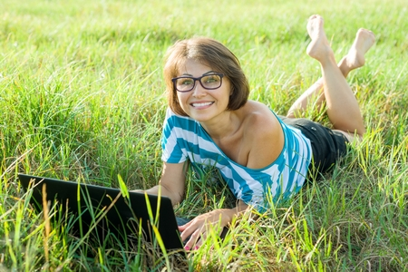Outdoor portrait smiling middle-aged woman freelancer blogger traveler with laptop on nature.