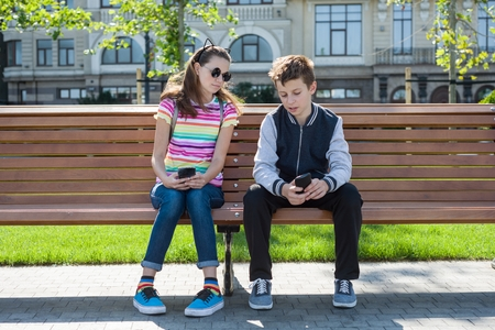 Boy and girl teenagers play, read, look at the smartphone. On the bench, the urban background. Rest, vacations, lifestyle of adolescent children