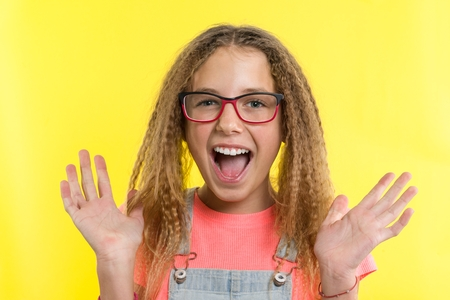Happy teenage girl blonde with curly hair gesticulating, bright yellow studio background Stock Photo