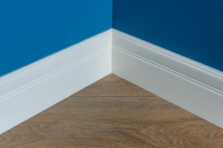 Moulding in the corner. Blue Matte Wall with laminate immitating oak texture.