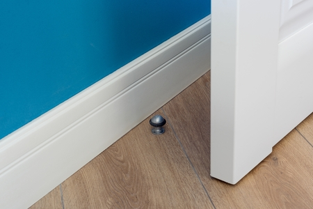 Close-up elements of the interior of the apartment. Metal chrome door stopper on laminate floor.