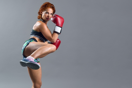 Athletic mature woman boxer with red gloves in sports clothes, guarding herself, getting ready to attack. Gray studio background, copy space