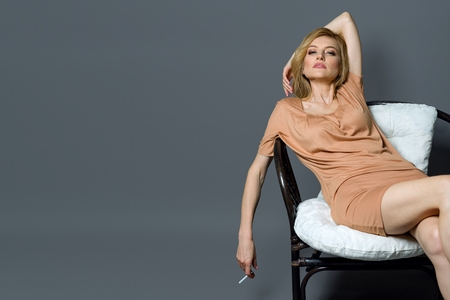Sexy mature blonde woman posing in a chair, holding a cigarette. Gray studio background, copy space Standard-Bild