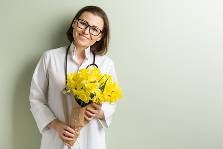 Smiling woman doctor with bouquet of flowers. World health day, doctors day. Copy space Stock Photo