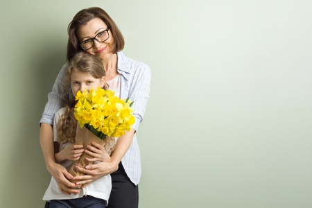 Child daughter congratulates mother and gives her bouquet of yellow narcissus flowers. Mom and girl smiling and hugging, spring family holiday concept. Mothers day. Copy space