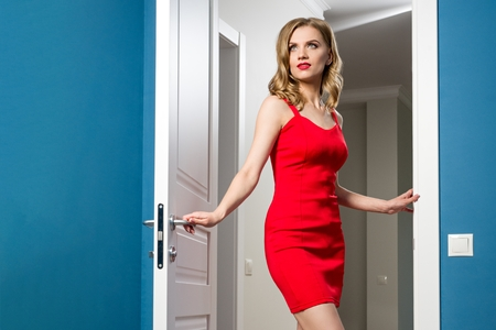 Fashionable young blonde girl in red dress opens a white interior door.