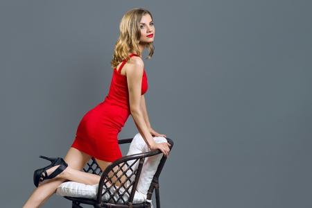 Modisches junges blondes Mädchen im roten Kleid auf Grau