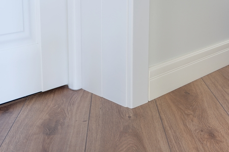 Moulding in the corner. Matte Wall with laminate immitating oak texture Imagens