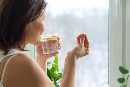 La mujer toma una pastilla con omega-3 y sostiene un vaso de agua fresca con limón. Imagen de la casa, por la mañana cerca de la ventana. Vitamina D, E, cápsulas de aceite de pescado. Nutrición, alimentación saludable, estilo de vida. Foto de archivo