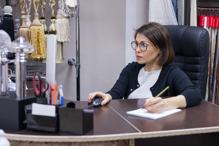 Businesswoman in the workplace, working at the computer. Office showroom interior fabrics, decor