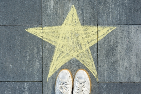Drawing of crayons on the asphalt - star and feet of woman Stock Photo