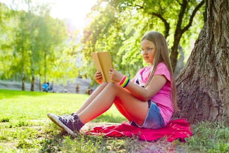 Girl child in glasses reading book in the park, on the grass near the tree Banque d'images