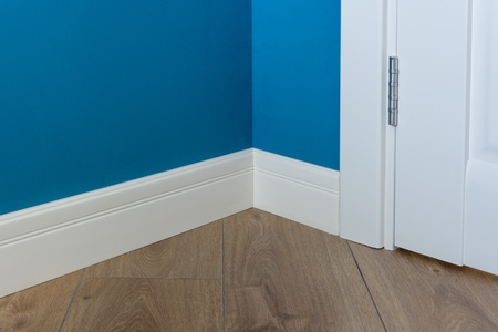 Moulding in the corner. Blue Matte Wall with laminated parquet floors immitating oak texture Imagens