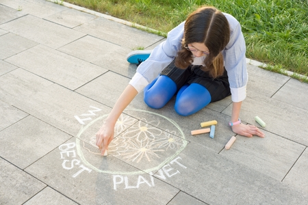 Teenage girl draws colored crayons on the asphalt drawing - my best planet Stock Photo