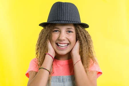 Portrait of laughing teen girl in hat, looking at the camera over yellow background