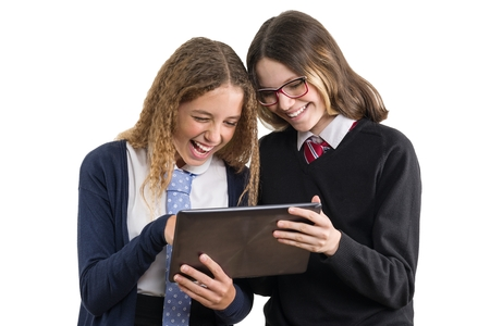 School girlfriends look at the tablet. Teenage girls in school uniform on white background, picture is isolated.