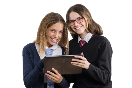 Happy high school friends closeup portrait. Teenage girls in school uniform on white background, with tablet, picture is isolated.