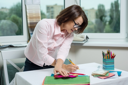 Interior designer, at the workplace in the office with samples of fabrics and accessories for curtains and upholstery.