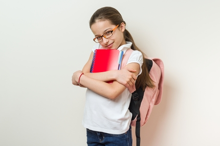 Portrait of a smiling schoolgirl 10 years old with glasses, with abackpack, notebooks. background bright wall in school