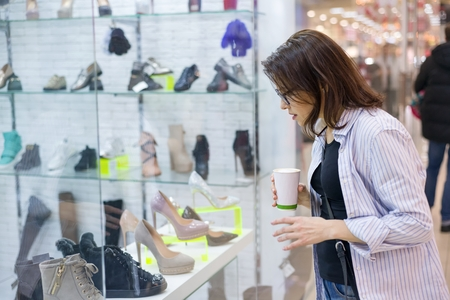 Middle-aged woman looks at the shoe showcase in the shopping mall