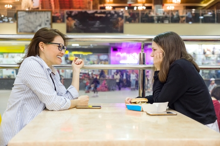 Communication of adult mother and teenage girl. Background table in cafe, in the shopping mall entertainment center. Lifestyle, leisure and people concept.