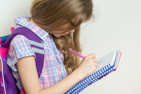 Girl child elementary school student wearing glasses with a backpack writing in her notebook. Bright school wall background