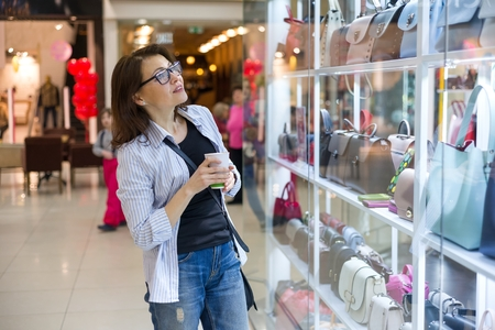 Adult woman looking at the showcase with bags and accessories in the shopping mall Stock Photo