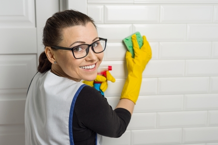 Portrait of cleaning service worker wearing protective rubber gloves, holding sponge and detergent, copy space.
