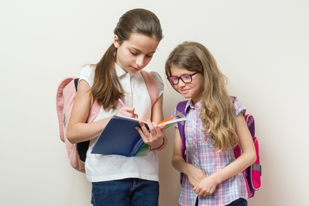 Communication of two girls at school. Schoolgirls with backpacks, books, background bright wall at school