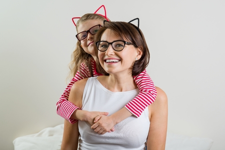 Daughter lovingly embraces her mother. Parent and child in glasses.
