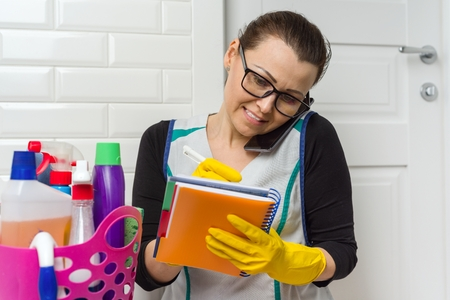 Housemaid woman is cleaning. Woman in yellow rubber gloves, talking on phone writing in notebook