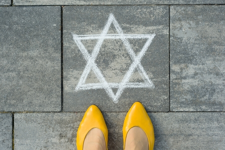 Female feet with abstract image of a six-pointed star, written on grey sidewalk Stock Photo