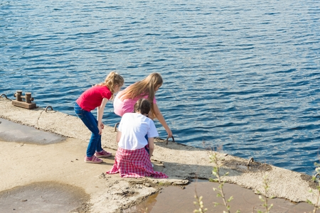 Children play near the river on the city embankment. View from above Stock Photo