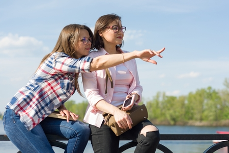 Outdoors portrait of female friends. Background nature, park, river. Women looking into the distance, pointing finger, copy space. Urban lifestyle and friendship concept. Stock Photo