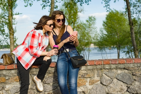 Happy two female friends watching photos, videos on the smartphone and having fun. Background nature, park, river. Urban lifestyle and friendship concept