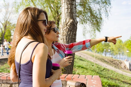 Outdoors portrait of female friends drinking coffee and having fun, women looking into the distance, pointing with fingers. Background nature, park, river. Urban lifestyle and friendship concept.