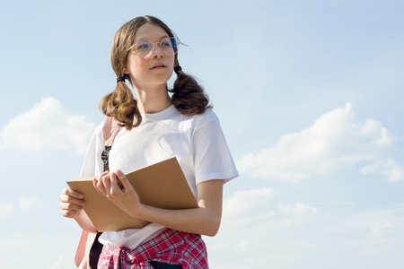 Teenage girl student wearing glasses with backpack reading book, sky background .