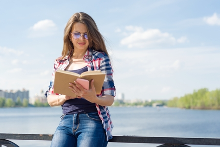 Outdoor portrait adult woman. Female reading book. Background street, city, river, copy space