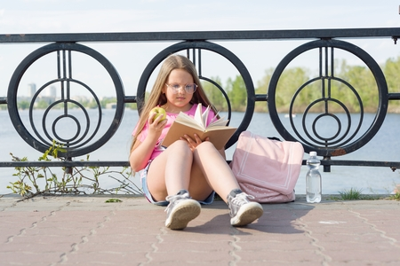 Child girl student wearing glasses with backpack is reading book. Urban background, river, sky Stock Photo
