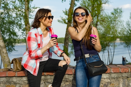 Outdoors portrait of female friends drinking coffee and having fun. Background nature, park, river. Urban lifestyle and friendship concept