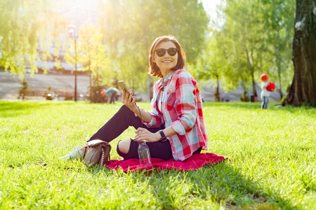 Mature woman listening to music on headphones. Sits on the grass in the park, resting enjoys nature.