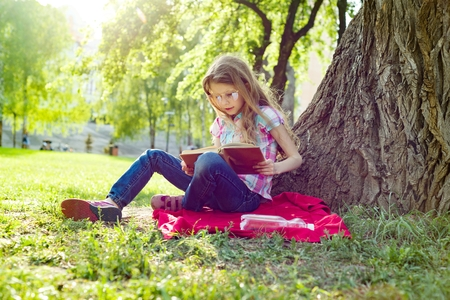 Girl child in glasses reading book in the park, on the grass near the tree.