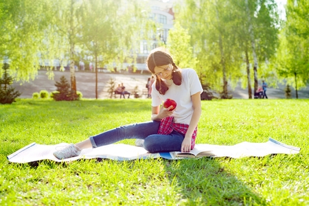 Girl student teenager resting and reading in park book. Stock Photo