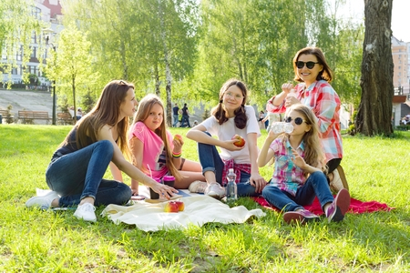 Rest in the park. Mothers with children sit on the grass, women drink coffee, children eat apples. Stock Photo