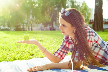 Young woman holding alarm clock in her hand, looking at the time. Background sunny city park, copy space