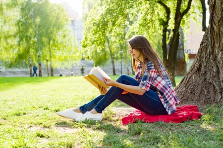 Beautiful woman with glasses reading book sitting on the grass near the tree in the park at sunset. Stock Photo