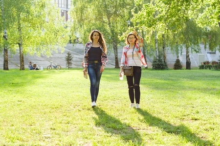 Two adult women walk through the city park at sunset Stock Photo